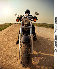 Biker on the country road against the sky