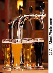 Four glasses of beer against beer tap