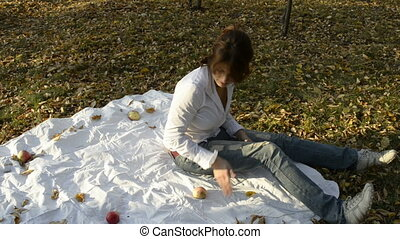 A young woman lay down on blanket with apples in autumn park