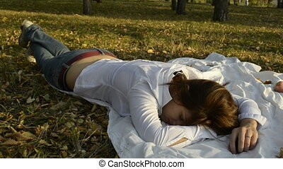 Young woman sleeping on a bedspread in the park and the...