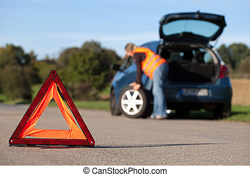 Tire change on a broken down car with a red warning triangle