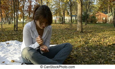 Young woman holding a rowan berries in autumn park