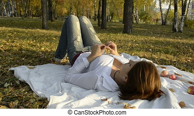 The young woman turned on bedspread in autumn park