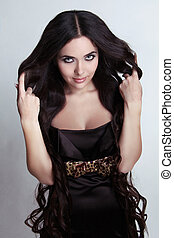 Smiling Brunette woman with long magnificent hair in black...