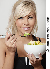 bowl of fresh fruit salad - sexy woman eating from a bowl of...