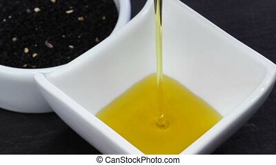 black cumin and black cumin oil is running into a bowl