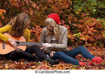 How to learn playing guitar - 2 girls are having fun in the...