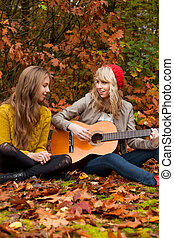 Girlfriends having a nice time with a guitar - 2 girls are...