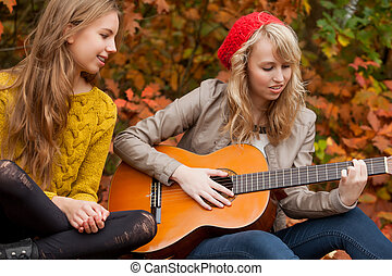 Playing guitar in the forest - 2 girls are having fun in the...