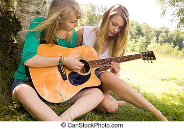 Learn to play guitar - Two girls are having fun in the...