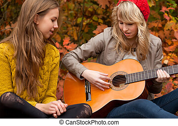 Sing a song with the guitar - 2 girls are having fun in the...