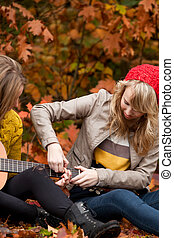 learning playing guitar - 2 girls are having fun in the...