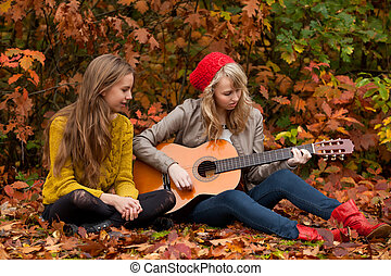 Playing guitar in the woods - 2 girls are having fun in the...