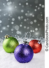 Colorful Christmas baubles on silver background with...