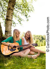 Girlfriends playing with the guitar - Two girls are having...