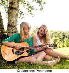 girls and the guitar - Two girls are having fun in the...