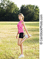 jogging - Young woman doing stretching outdoors, smiling and...
