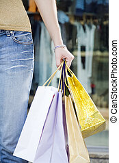 Shopping - Cropped view of woman holding shopping bags
