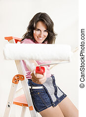 new house - Young woman holding paint roller and smiling