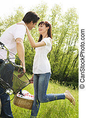 meadow - couple in park with holding picnic basket, kissing...