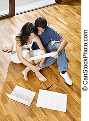 new house - Young Hispanic couple looking at blueprints of...