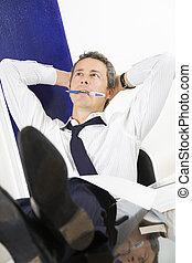 Bureau - Mature businessman relaxing in office, leaning feet...