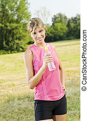 jogging - Young woman about to drink from water bottle...