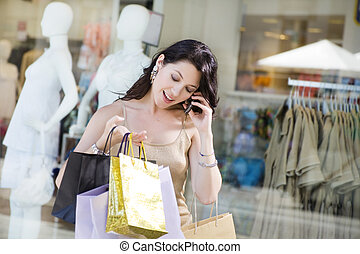 Shopping - Mid adult Italian woman on the phone and holding...