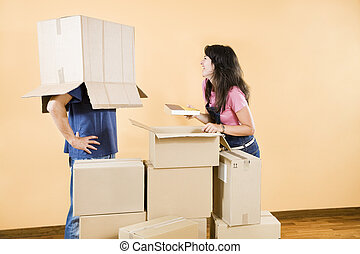 new house - Young couple being silly with moving boxes at...