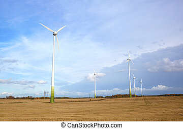 Go green! - Many wind turbines, green grass and blue sky...