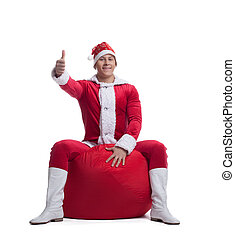 Young man santa claus sit on red bag with presents