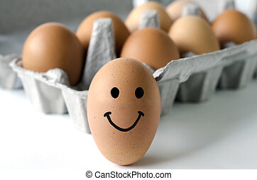 Organic eggs - A smily egg outside a tray of freshly laid...