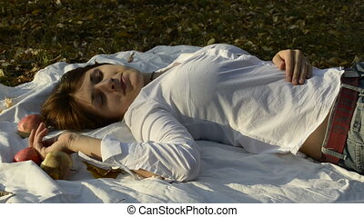 Young woman lying on bedspread