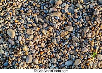 pebbles stones of etretat beach in normandie france -...