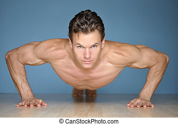 Pushup - Handsome muscular man looks at camera while...