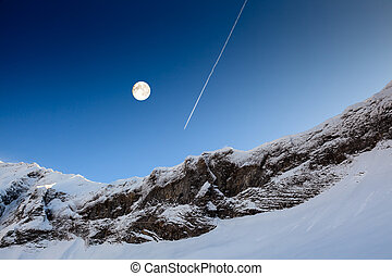 Full Moon and Airplane Trail in Blue Sky above Mountain...