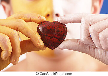 heart - A heart of a gem stone in the hands of children