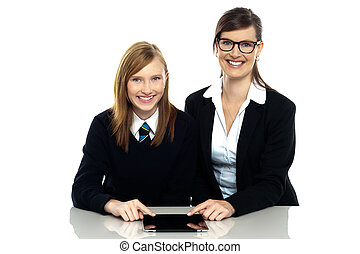 Tutor and student duo operating tablet pc Facing camera and...