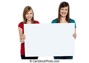 Gorgeous women presenting blank ad board isolated over white...