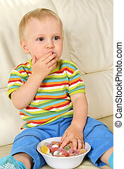 boy eating sweets - Little boy eating sweets. full bowl of...