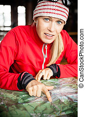 Woman hiker with map planning trip, inside cold shelter or...