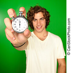 Man Holding Stopwatch On Green Background