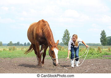 Young blonde woman commanding chestnut horse to lie down on...