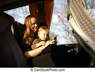 Mother and kid are playing game on the phone. - Young mother...