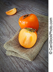 Persimmon - Bunch of fresh persimmon fruit on a wooden...