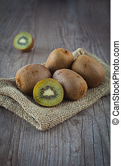 Kiwi - Bunch of fresh kiwi fruit on a wooden background