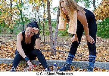 Two women athletes taking a break
