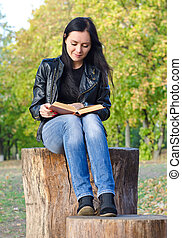 Woman sitting on a tree stump reading - Attractive trendy...