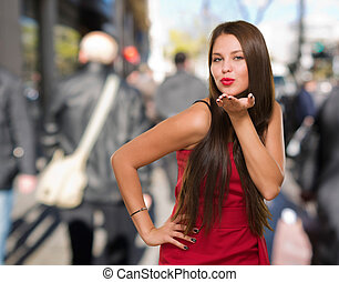 Beautiful Young Woman Blowing A Kiss against a street...