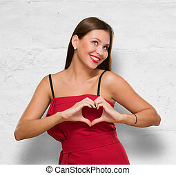 Beautiful Woman Making Heart Shape Sign against a concrete...